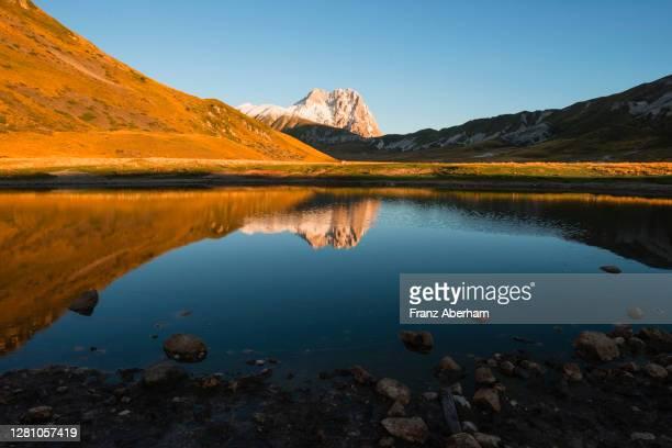 reflection of corno grande in pond, campo imperatore, italy - parco nazionale del gran sasso e monti della laga foto e immagini stock
