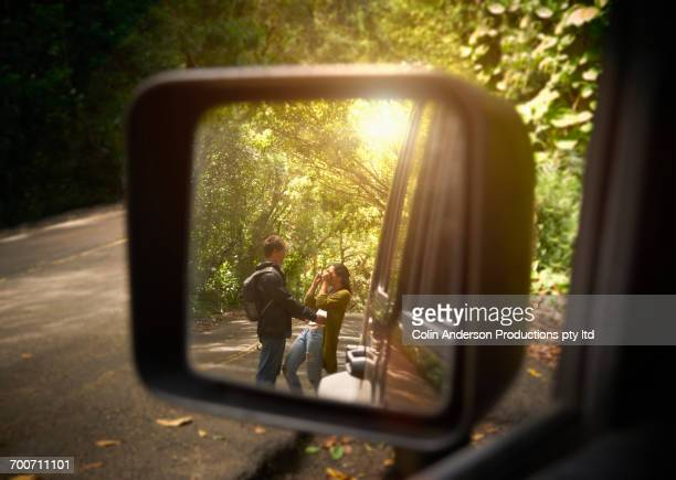 Reflection of couple in side-view mirror of car