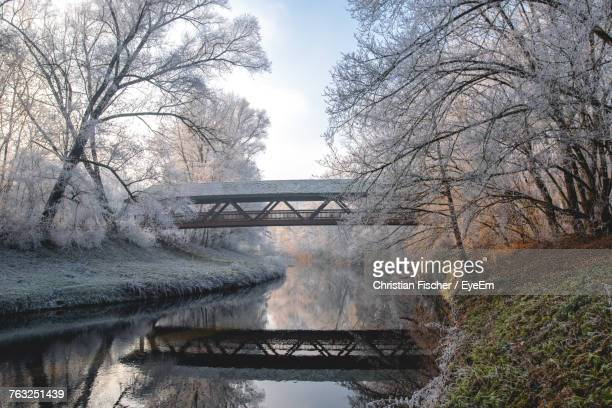 reflection of covered bridge on river in forest during winter - covered bridge stock photos and pictures