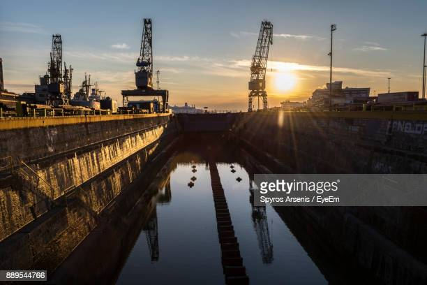 reflection of crane in water against sky during sunset - piraeus stock photos and pictures