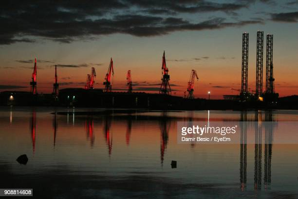 Reflection Of Cranes In Lake Against Orange Sky During Sunset