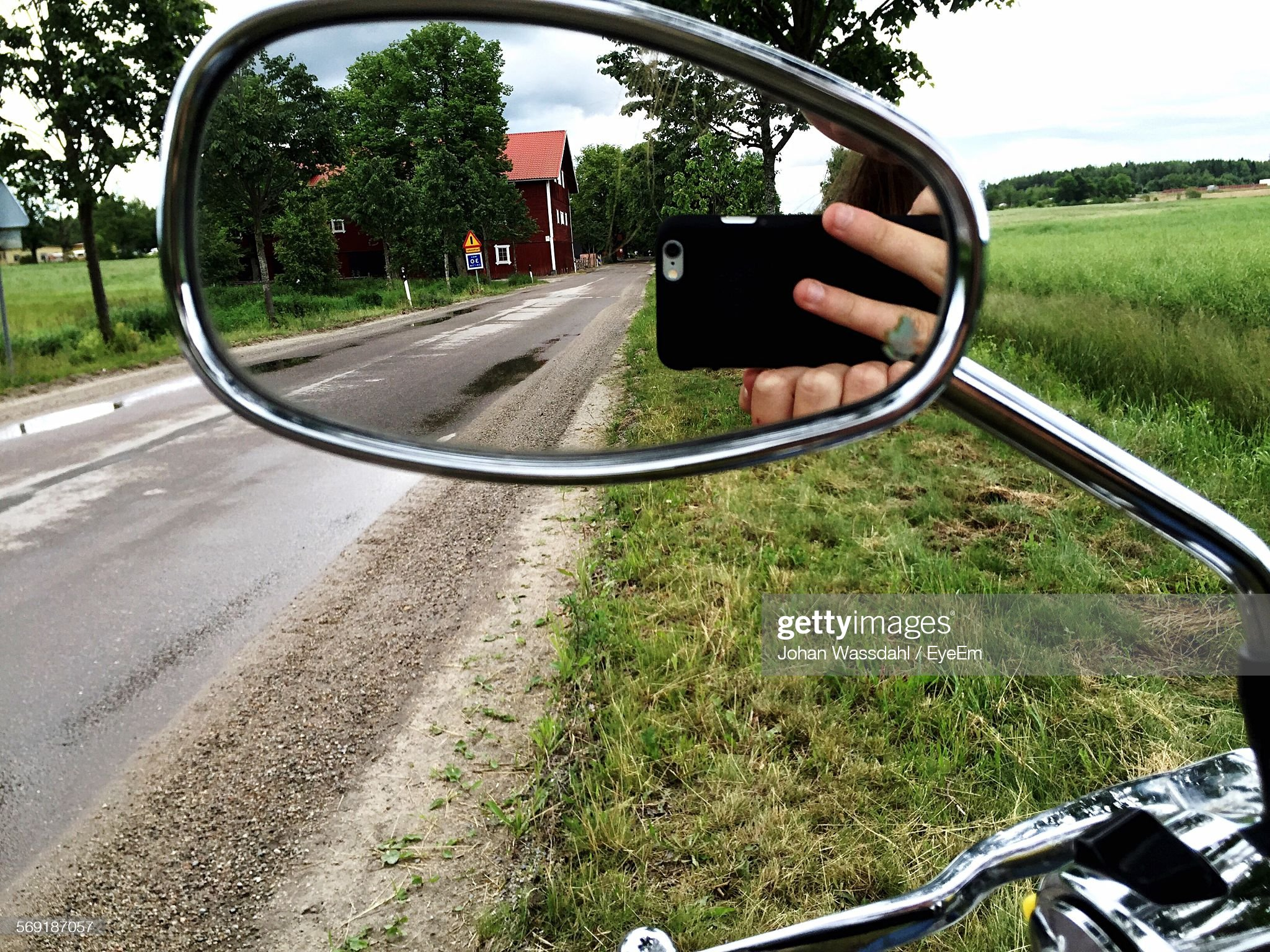 Reflection of cropped man photographing through smart phone on side-view mirror : Stock Photo
