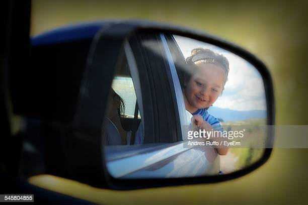 Reflection Of Cute Smiling Girl In Side-View Mirror