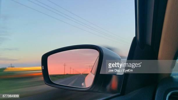 Reflection Of Empty Street During Sunset On Rear-View Mirror