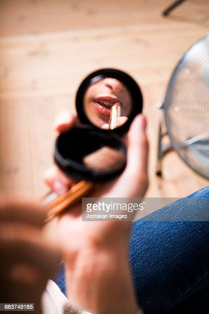 reflection of fashion model applying lipstick in mirror at studio - powder compact stock pictures, royalty-free photos & images