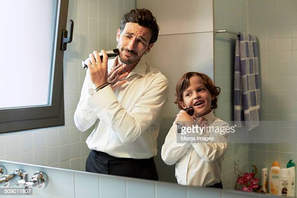 Reflection of father and son shaving together