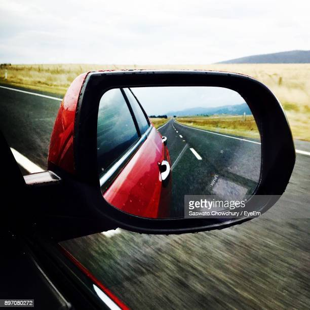 Reflection Of Field And Road On Side-View Mirror Of Car