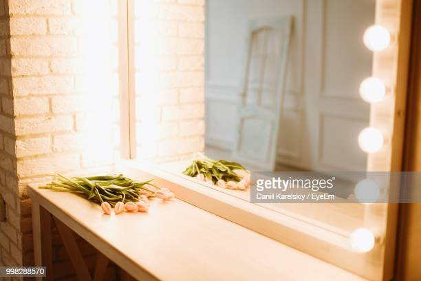 reflection of flowers in illuminated mirror - dressing table stock photos and pictures