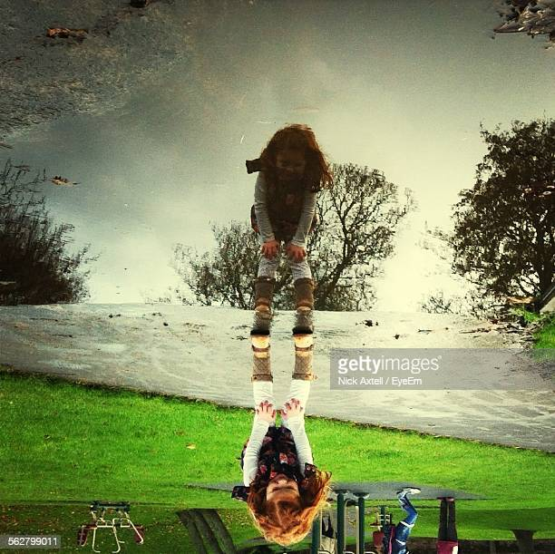Reflection Of Girl In Puddle At Park