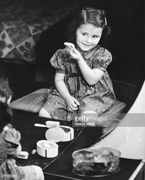 Reflection of girl (4-5) sitting in front of mirror, applying face powder (B&W), elevated view