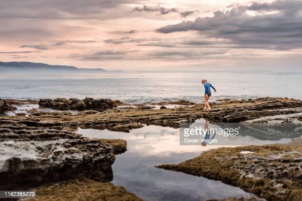 reflection of girl walking near tidal pools at the coast at dusk - tidvattensbassäng bildbanksfoton och bilder