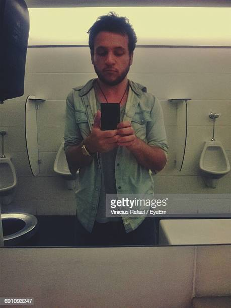 Reflection Of Handsome Man Taking Selfie In Public Restroom On Mirror
