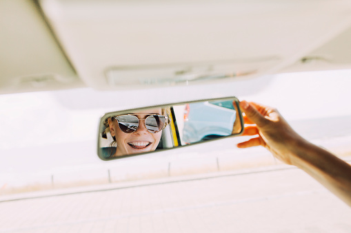 Reflection of happy young woman in rear-view mirror of a car - gettyimageskorea
