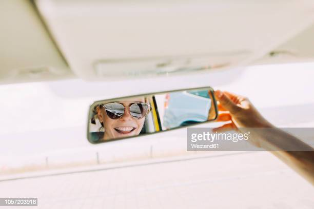 reflection of happy young woman in rear-view mirror of a car - auto stockfoto's en -beelden