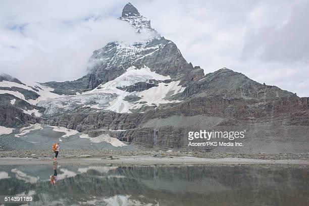Reflection of hiker in lake below Matterhorn