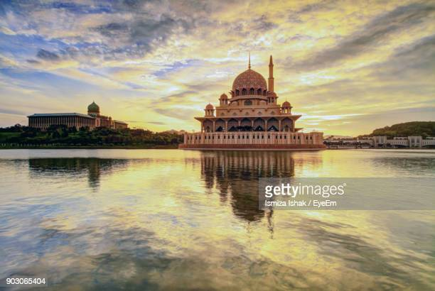 Reflection Of Historic Mosque On Lake Against Cloudy Sky