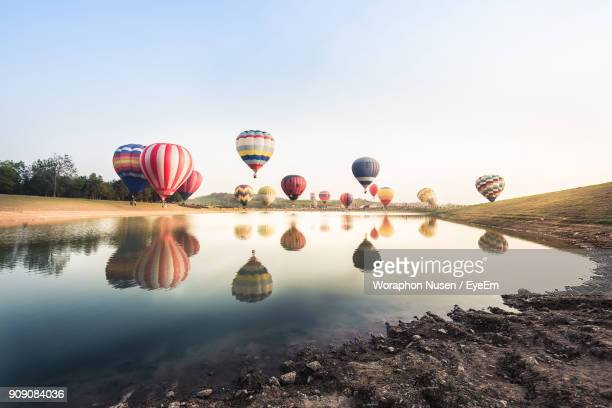 reflection of hot air balloons on lake against sky - hot air balloon stock pictures, royalty-free photos & images