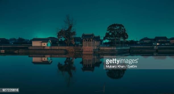 Reflection Of Houses And Trees In River Against Blue Sky At Dusk