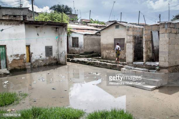 reflection of houses in puddle against sky - environmental damage stock pictures, royalty-free photos & images