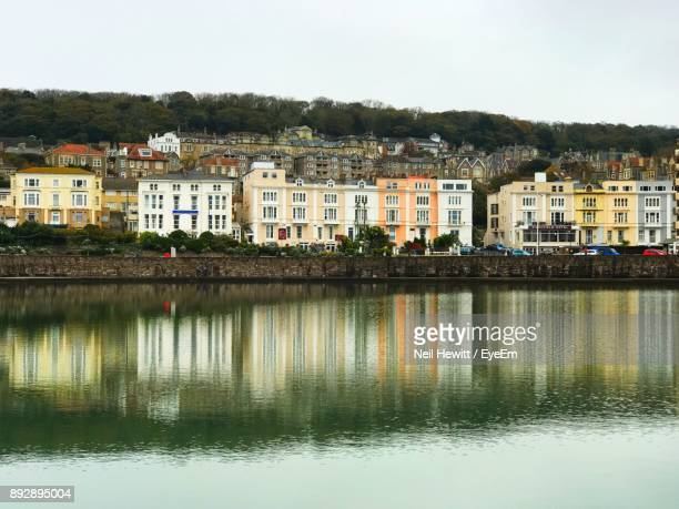 reflection of houses in water against clear sky - weston super mare stock pictures, royalty-free photos & images