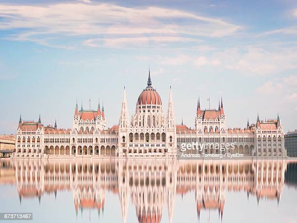 reflection of hungarian parliament building in river against sky - budapest stock pictures, royalty-free photos & images