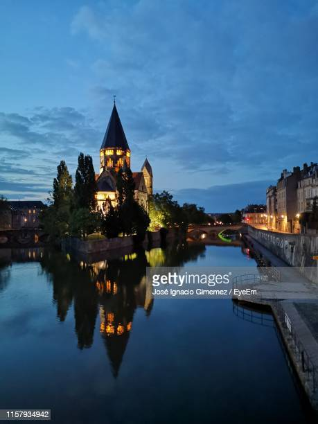 reflection of illuminated buildings in calm river at night - lorraine stock pictures, royalty-free photos & images