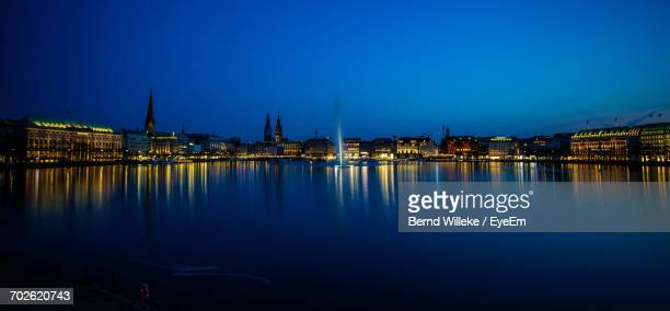 Reflection Of Illuminated Buildings In Calm Water At Night