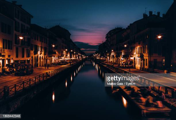 reflection of illuminated buildings in canal at night - milan stock pictures, royalty-free photos & images