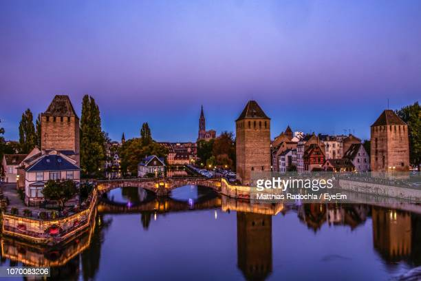 reflection of illuminated buildings in city at night - strasbourg stock pictures, royalty-free photos & images