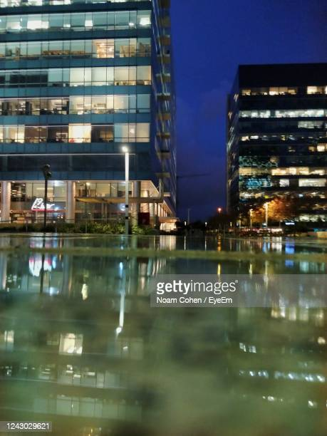 reflection of illuminated buildings in city at night - noam cohen stock pictures, royalty-free photos & images