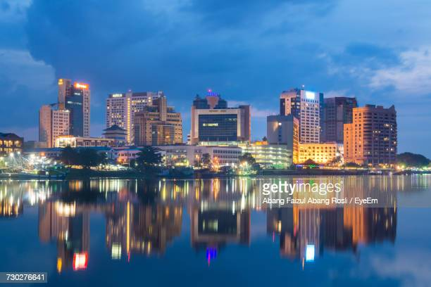 reflection of illuminated buildings in city at night - sarawak state stock pictures, royalty-free photos & images