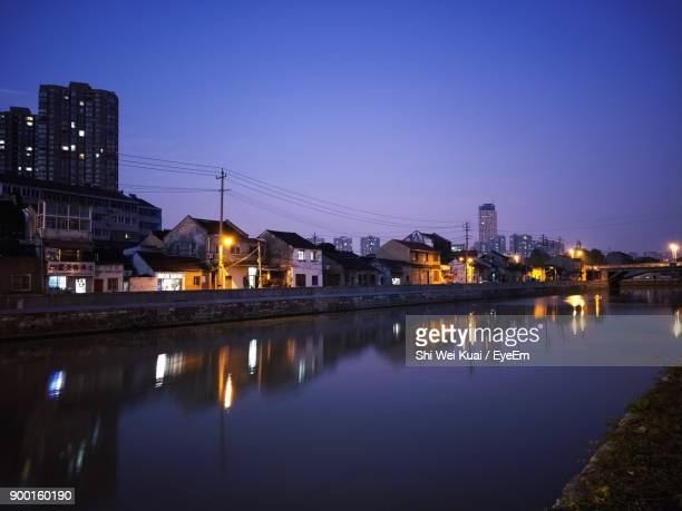 reflection of illuminated buildings in city at night - changzhou stock pictures, royalty-free photos & images