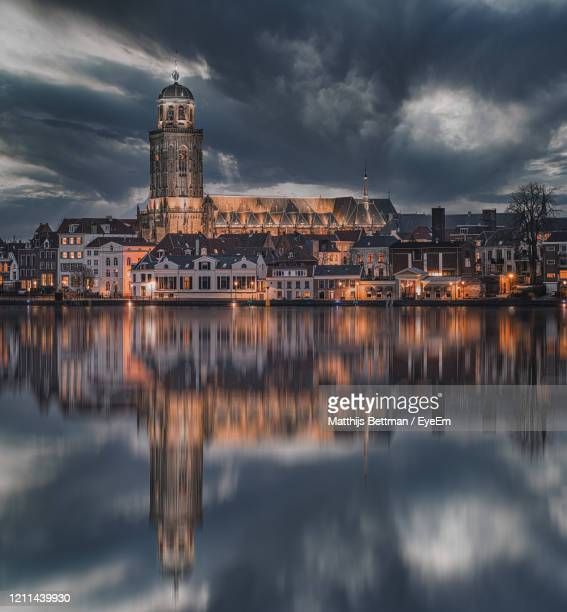 reflection of illuminated buildings in lake against sky - overijssel stock pictures, royalty-free photos & images