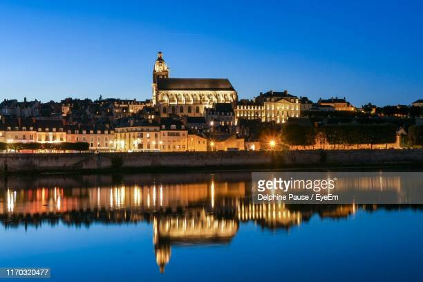 reflection of illuminated buildings in lake - loir et cher stock pictures, royalty-free photos & images