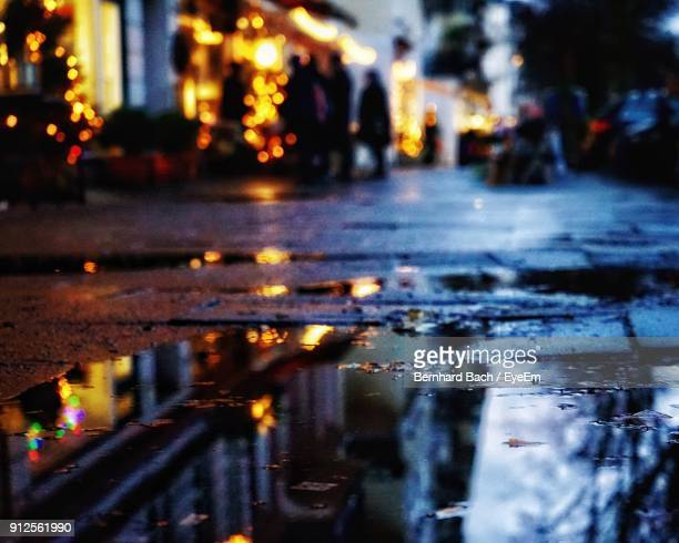 Reflection Of Illuminated Buildings In Puddle