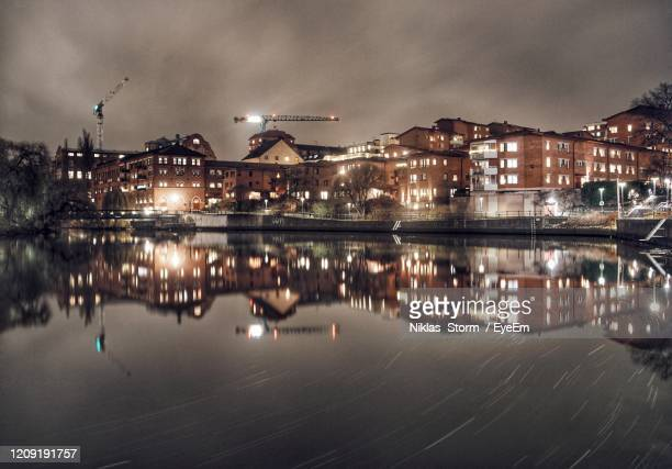 reflection of illuminated buildings in river at night - norrkoping fotografías e imágenes de stock