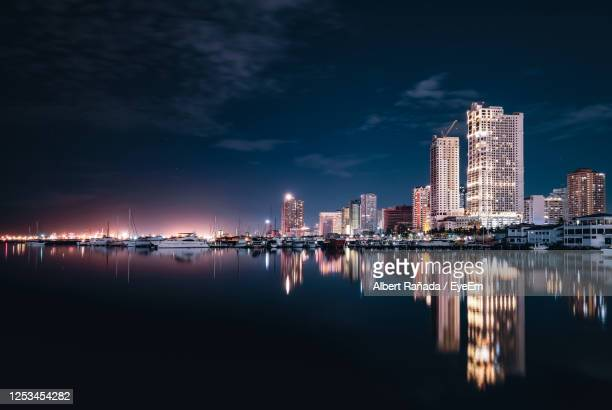 reflection of illuminated buildings in river at night - manila philippines stock pictures, royalty-free photos & images