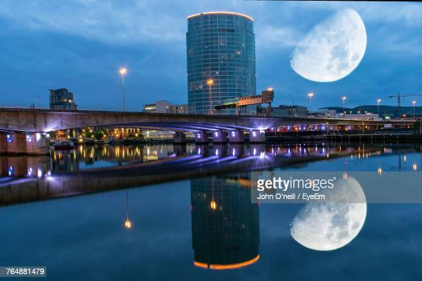 reflection of illuminated buildings in water at night - belfast stock pictures, royalty-free photos & images