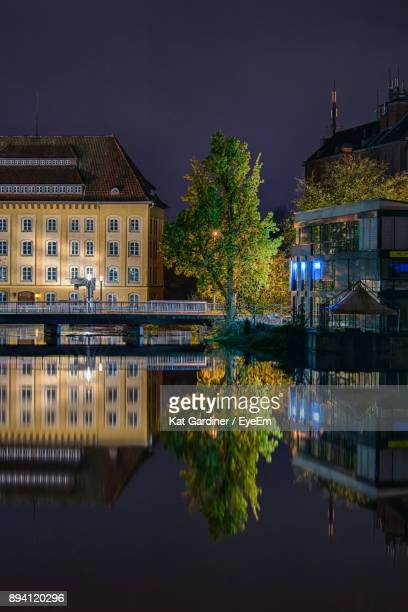 reflection of illuminated buildings in water at night - celle stock photos and pictures