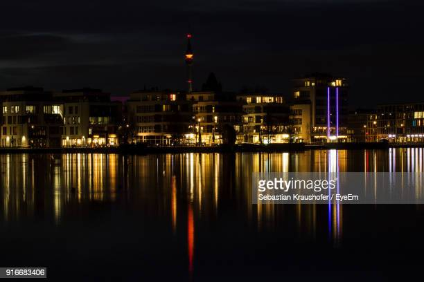 reflection of illuminated buildings in water at night - sebastian kraushofer stock-fotos und bilder