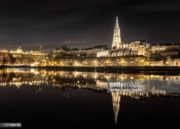 reflection of illuminated buildings in water - sandra gygax stock-fotos und bilder
