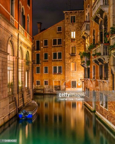 reflection of illuminated buildings on canal at night - heather cole stock pictures, royalty-free photos & images