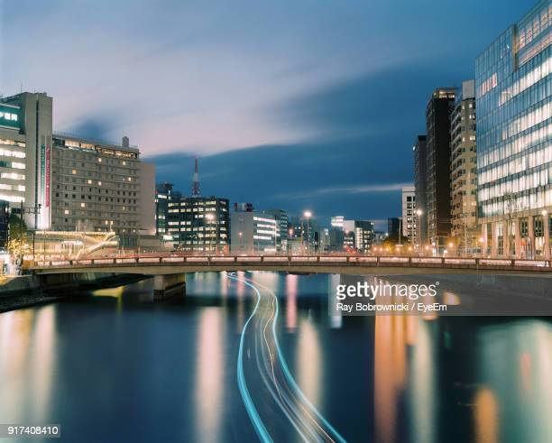 reflection of illuminated city in water at night - fukuoka city stock pictures, royalty-free photos & images
