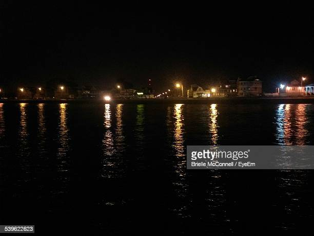 reflection of illuminated city on lake against sky at night - mcconnell stock pictures, royalty-free photos & images