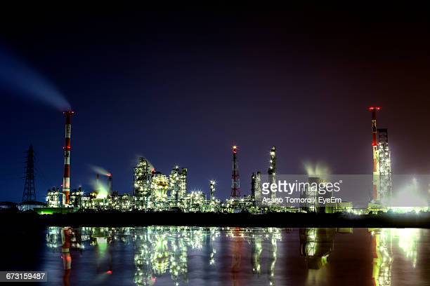reflection of illuminated factory on river against sky at night - mie prefecture stock pictures, royalty-free photos & images