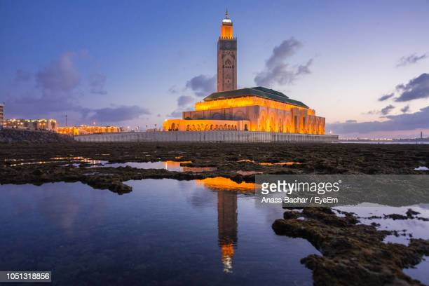 Reflection Of Illuminated Historic Mosque On Sea Against Sky