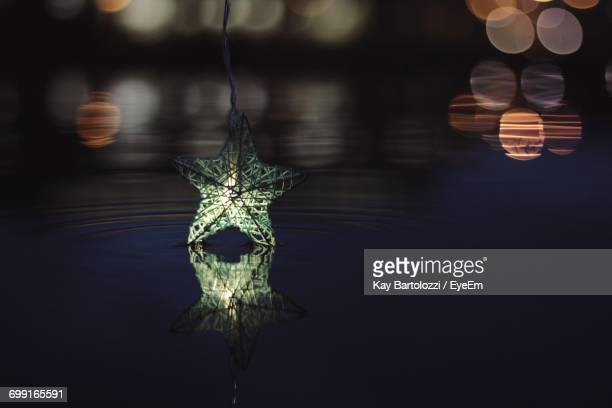 reflection of illuminated star shape decoration on lake at night - stars and strings stock photos and pictures