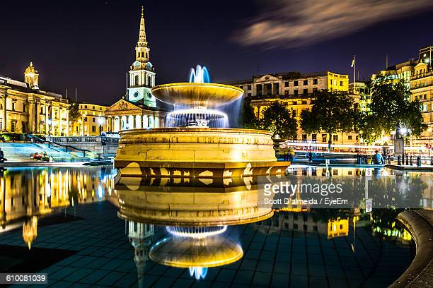 reflection of illuminated trafalgar square in pond at night - trafalgar square stock pictures, royalty-free photos & images