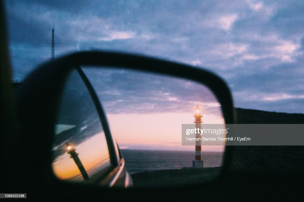 Reflection Of Light House Seen On Side-View Mirror Of Car During Sunset : Stock Photo