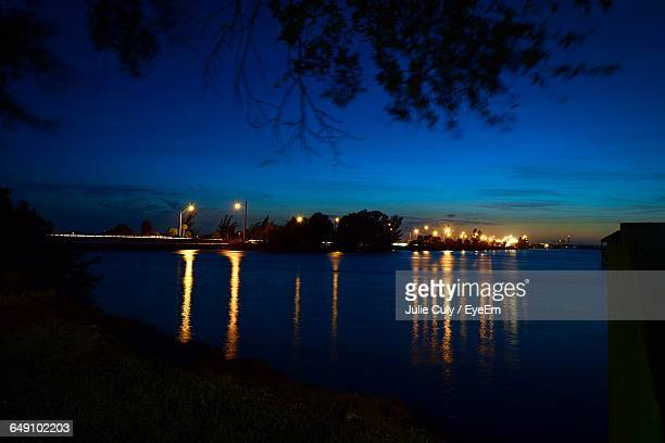 reflection of light in river against blue sky at dusk - julie culy stock pictures, royalty-free photos & images